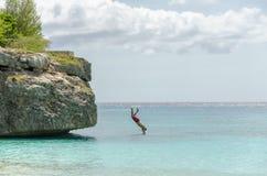 El turista que salta de la roca en la playa magnífica de Knip Imágenes de archivo libres de regalías