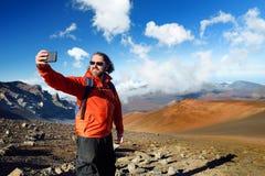 El turista que toma una foto de sí mismo en cráter del volcán de Haleakala en las arenas de desplazamiento se arrastra, Maui, Haw Imagen de archivo libre de regalías