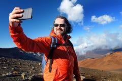 El turista que toma una foto de sí mismo en cráter del volcán de Haleakala en las arenas de desplazamiento se arrastra Se llenan  Fotografía de archivo