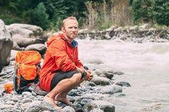 El turista restaura en la orilla del río de la montaña Imagenes de archivo