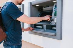 El turista retira el dinero de la atmósfera para el viaje adicional Finanzas, tarjeta de crédito, retiro del dinero Estilo de vid fotografía de archivo libre de regalías