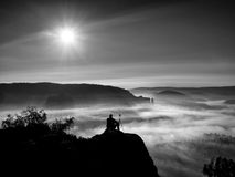 El turista se sienta en el pico de la roca y de la observación de la piedra arenisca en la niebla y la niebla en valle de la maña Imágenes de archivo libres de regalías