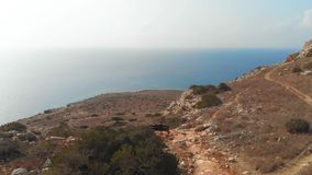 El turista se sienta en un banco en el lado de una montaña y la mirada en la distancia, en el fondo del mar hermoso metrajes