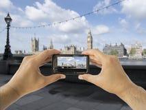 El turista soporta el móvil de la cámara en ben grande fotografía de archivo