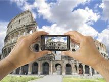El turista soporta el móvil de la cámara en el coliseo en Roma foto de archivo libre de regalías