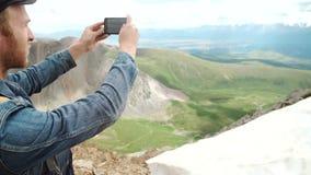 El turista toma las fotos con el teléfono elegante en el pico de la roca almacen de metraje de vídeo