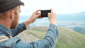 El turista toma las fotos con el teléfono elegante en el pico de la roca almacen de video