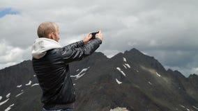 El turista toma las fotos con el teléfono elegante en el pico de la roca metrajes
