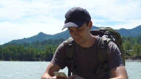El turista utiliza el teléfono en las montañas almacen de metraje de vídeo
