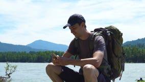 El turista utiliza el teléfono en las montañas almacen de video