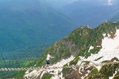 El turista va en un puente de cuerda estirado sobre la garganta a la estación de esquí Foto de archivo libre de regalías