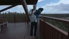 El turista viene a los prismáticos en torre de la visión almacen de video