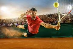 El un jugador de salto, hombre apto del caucásico, jugando a tenis en la corte de tierra con los espectadores foto de archivo