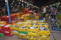 El un montón de industrias pesqueras en cestas está esperando la compra en el mercado de los mariscos de la noche de la venta al  Fotografía de archivo