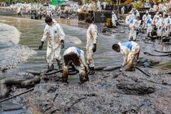 El un montón de trabajadores está intentando quitar el derrame de petróleo Foto de archivo libre de regalías