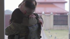El uniforme militar que llevaba del hombre joven vino casero y feliz abrazando a su esposa alegre hermosa en el fondo de la calle almacen de video