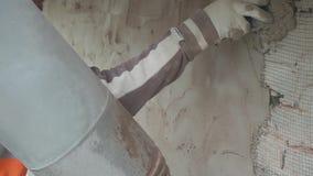 El uniforme que lleva y los guantes del trabajador de sexo masculino enyesa la pared con el cuchillo del spackle metrajes