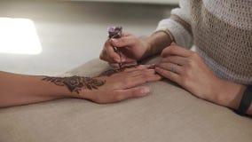 El upcshot cercano de las manos del ` un s de la mujer en una mano bronceada aplica un tatuaje floral de la alheña almacen de video