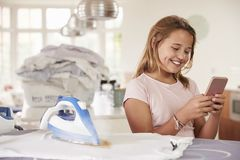 El usar de la chica joven distraído por el teléfono mientras que plancha imágenes de archivo libres de regalías