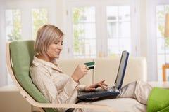 El usar de la mujer de la tarjeta de crédito en Internet. Imágenes de archivo libres de regalías