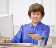 El usar de la mujer de la tarjeta de crédito hacer compras en línea Imagen de archivo