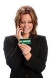 El usar de la mujer de la tarjeta de crédito mientras que en el teléfono celular Foto de archivo libre de regalías