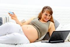 El usar de la mujer embarazada de la tarjeta de crédito hacer compras de red Imagenes de archivo