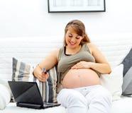 El usar de la mujer embarazada de la tarjeta de crédito hacer compras de red Imagen de archivo