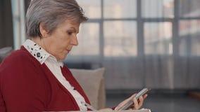 El usar de la señora mayor celular y el sentarse en casa almacen de metraje de vídeo