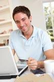 El usar del hombre joven de la tarjeta de crédito en el Internet imagen de archivo