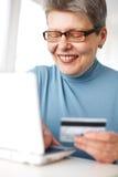 El usar mayor de la mujer de la tarjeta de crédito y computadora portátil Fotos de archivo libres de regalías