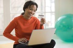 El usar negro de la mujer de la tarjeta de crédito y computadora portátil Foto de archivo