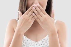 El uso asiático de la mujer ambas manos cierra la boca para no hacer ninguna observación respecto Imagenes de archivo