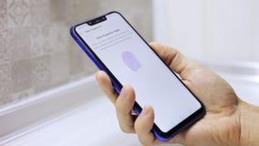 El uso del uso de la mano del hombre del primer en el smartphone, el hombre se aplica el finger al escáner, el programa reconoce almacen de metraje de vídeo