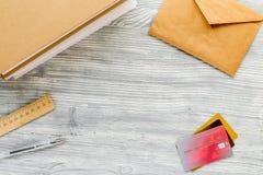El uso del estudiante fijó con las tarjetas, el teclado y el sobre de crédito en la maqueta de escritorio blanca de la visión Imágenes de archivo libres de regalías