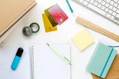El uso del estudiante fijó con las tarjetas, el teclado y el sobre de crédito en la maqueta de escritorio blanca de la visión imagen de archivo