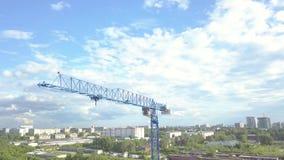 El vídeo aéreo de una grúa de construcción aumentada contra el cielo azul y de las nubes blancas en un día de verano en el solar  metrajes