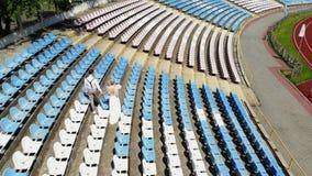 El vídeo aéreo, en el estadio, los recienes casados en casarse el traje está caminando entre los asientos blancos y azules Primav metrajes