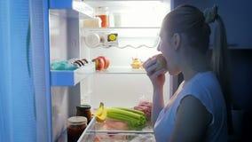 El vídeo de la cámara lenta de la mujer joven en pijamas come la manzana en cocina en la noche almacen de metraje de vídeo