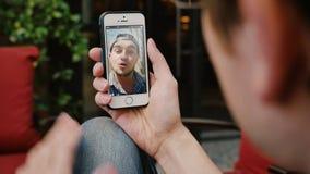 El vídeo del hombre charla con el amigo masculino en Smartphone
