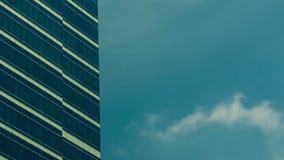 El vídeo del lapso de tiempo del sol y de nubes brillantes reflejó en bulding de cristal corporativo almacen de video