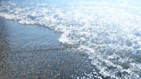 el vídeo del primer 4k del mar apacible agita el funcionamiento en orilla arenosa en el día soleado Agua clara azul en la playa E almacen de metraje de vídeo
