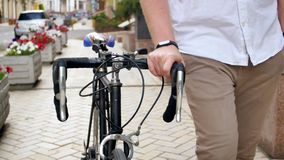 el vídeo 4k del estudiante joven que camina con viejos deportes monta en bicicleta en la calle almacen de video