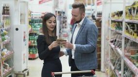 El vídeo positivo divertido de pares felices jovenes está haciendo compras en el supermercado metrajes