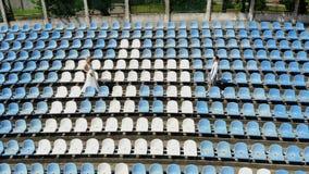 El v?deo a?reo, en el estadio, los recienes casados en casarse el traje est? caminando entre los asientos blancos y azules Primav metrajes