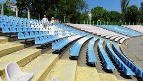El v?deo a?reo, en el estadio, los recienes casados en casarse el traje est? caminando entre los asientos blancos y azules Primav almacen de video