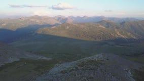El valle verde hermoso rodeado por las colinas boscosas y las cuestas de montaña soleadas cubrió clip metrajes