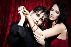 El vampiro masculino está mordiendo a una mujer Imagen de archivo libre de regalías