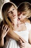 El vampiro masculino está mordiendo a una mujer joven con un blanco fotografía de archivo