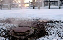 El vapor del primer es de cubierta sanitaria de la alcantarilla en nieve en parque del invierno Nieve derretida alrededor imagenes de archivo